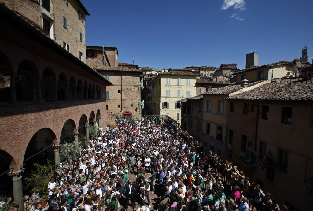 The Oca (Goose) neighborhood horse Quadrivia and his jockey Enrico Bruschelli, center, receive the blessing prior to the start of the ancient Palio of Siena, the famous break-neck bareback horse race run, in Siena, Italy, August 17. AP Photo/Paolo Lazzeroni