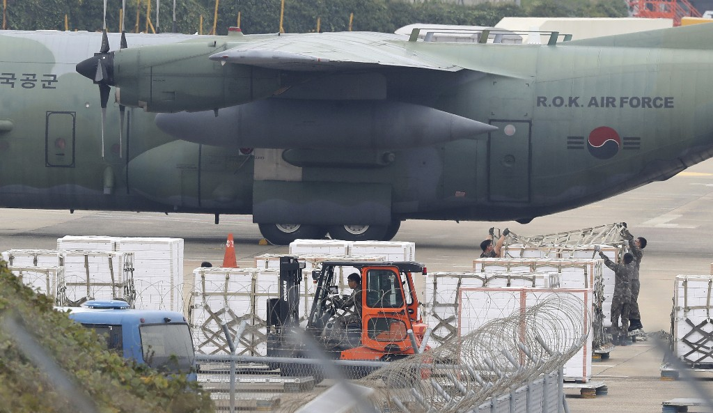 In this Nov. 11, 2018 photo, South Korean soldiers prepare to load boxes of tangerines near South Korea's Air Force cargo plane C-130 at the Jeju International Airport on Jeju Island, South Korea. South Korea has airlifted thousands of boxes of tangerines to North Korea in return for the North's large shipments of pine mushrooms in September.(Park Ji-ho/Yonhap via AP)
