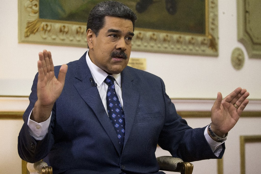 Venezuela's President Nicolas Maduro speaks during an interview with The Associated Press at Miraflores presidential palace in Caracas, Venezuela, Thursday, Feb. 14, 2019. Maduro is inviting a U.S. special envoy to come to Venezuela after revealing during the interview that his foreign minister recently held secret meetings with the U.S. official in New York. (AP Photo/Ariana Cubillos)