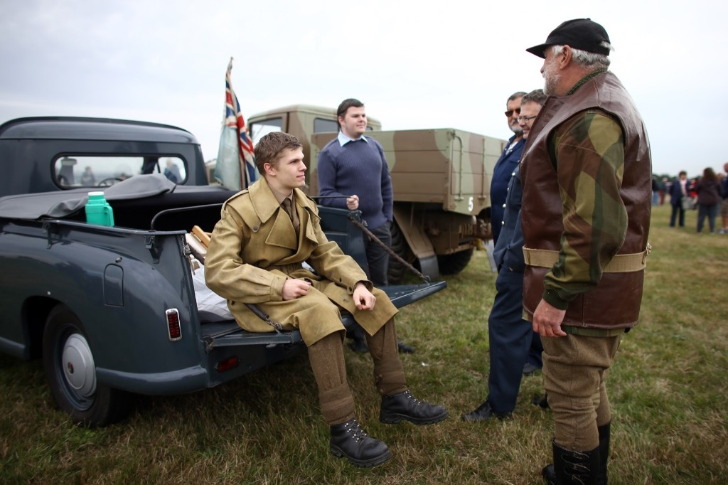 Historical reenactors chat next to vintage vehicles, Tuesday, in Biggin Hill, England. Carl Court/Getty Images