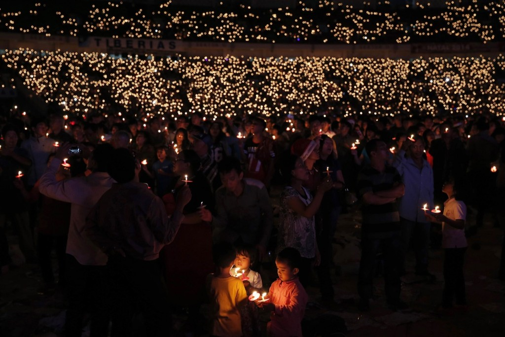 Indonesian Christians hold candles during a Christmas mass prayer session at Gelora Bung Karno stadium in Jakarta. REUTERS/Beawiharta