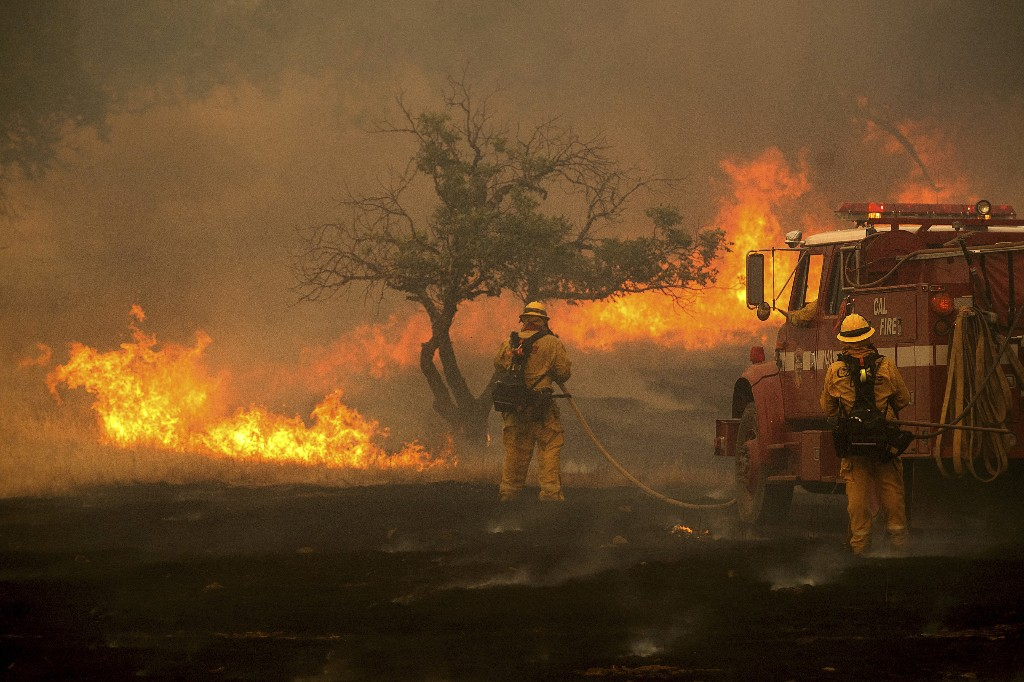 A firefighter battles the River Fire as it tears through Lakeport, Calif., on Monday, July 30, 2018. A pair of wildfires that prompted evacuation orders for thousands of people are barreling toward small lake towns in Northern California. (AP Photo/Noah Berger)