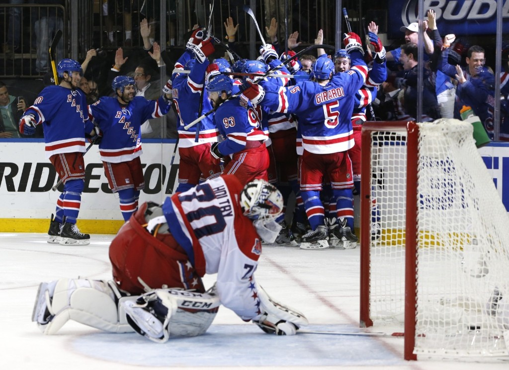 The New York Rangers celebrate the game-winning goal by Derek Stepan against Washington as Capitals goalie Braden Holtby looks at the puck in the net during overtime of Game 7. AP Photo/Kathy Willens