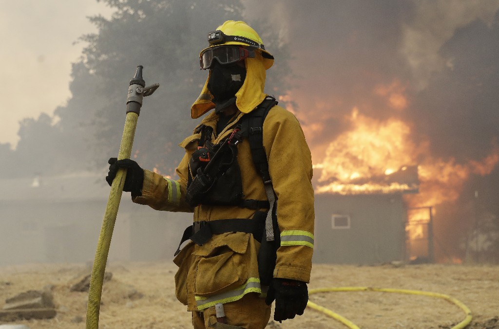 A firefighter with Pacifica Fire Department stands in front of a burning barn to prevent it from reaching a residence, Monday, July 30, 2018, in Finley, Calif. (AP Photo/Marcio Jose Sanchez)