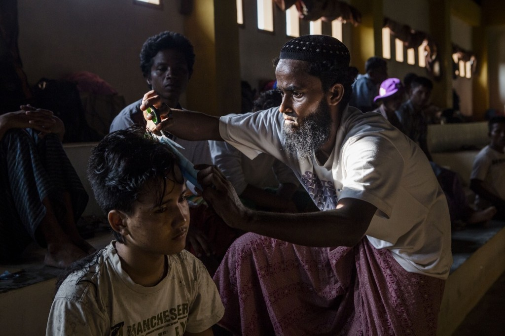 An Rohigya migrant helps cut his friend's hair inside a shelter in Lhoksukon, Aceh province, Indonesia. Ulet Ifansasti/Getty Images
