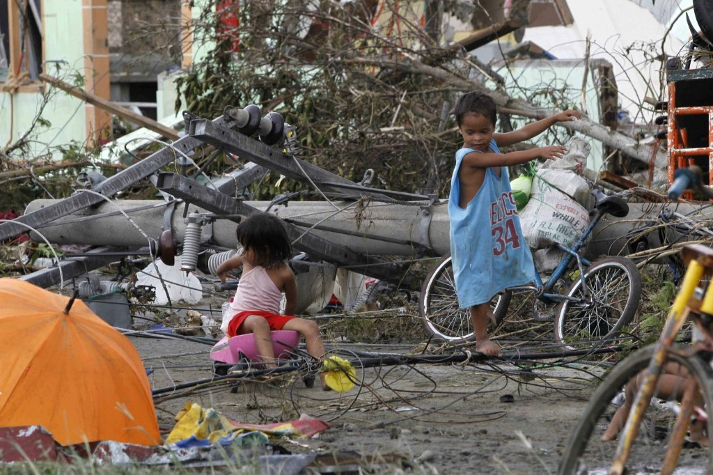 Children play near electric posts that were damaged after super Typhoon Haiyan battered Tacloban city. REUTERS/Romeo Ranoco
