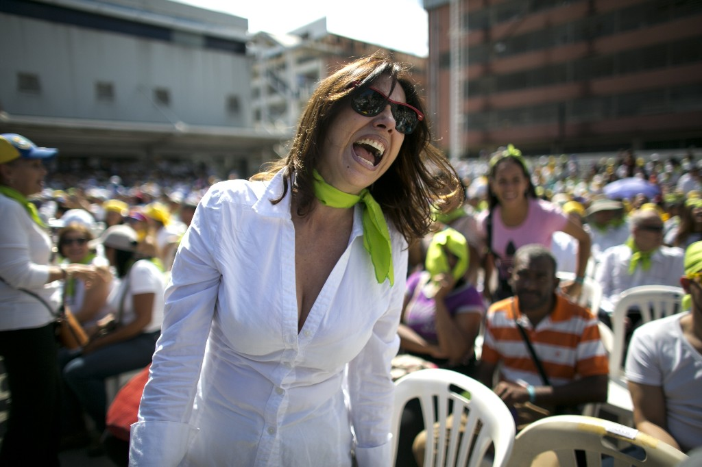 A woman yells during an event to swear in nurses, doctors, professionals and others, as the group that will help with the arrival and distribution of humanitarian aid in Venezuela, in Caracas, Venezuela, Saturday, Feb. 16, 2019. The U.S. Air Force has begun flying tons of aid to a Colombian town on the Venezuelan border as part of an effort meant to undermine socialist President Nicolas Maduro. The first of three C-17 cargo planes has flown from Homestead Air Reserve Base in Florida and landed in the town of Cucuta.(AP Photo/Ariana Cubillos)