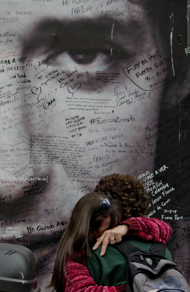Fans of Argentine musician Gustavo Cerati in front of a poster with his image in Buenos Aires. Cerati died at the age of 55 last Thursday. AP Photo/Natacha Pisarenko