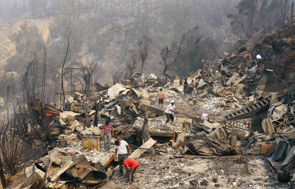 Residents survey the damage where a forest fire burned several neighbourhoods in Valparaiso. At least 11 people were killed and 500 houses destroyed. REUTERS/Eliseo Fernandez