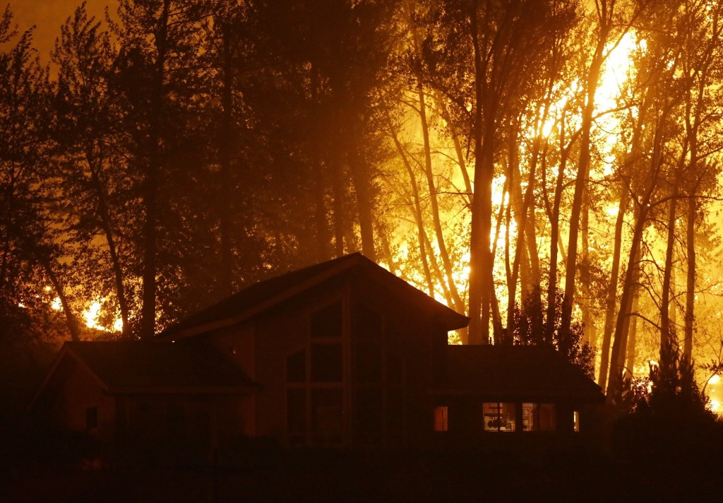 A wildfire burns behind a home in Twisp, Wash. AP Photo/Ted S. Warren