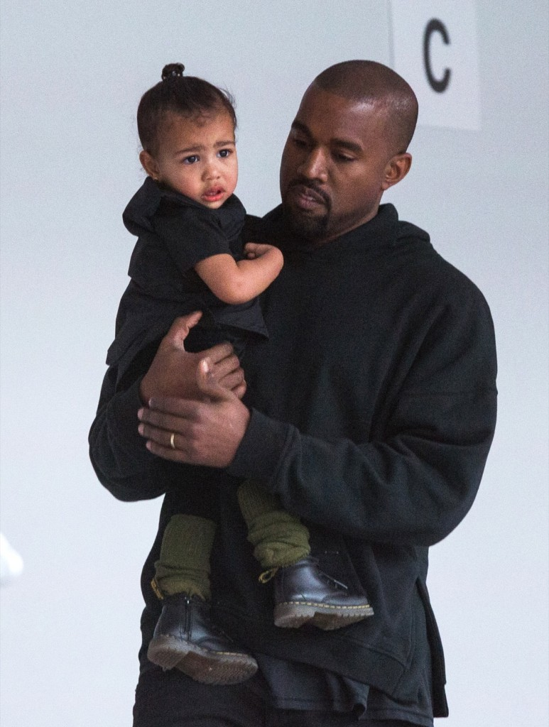 Kanye West carries his daughter, North, while preparing for a presentation of his Fall/Winter 2015 partnership with Adidas at New York Fashion Week, Thursday. REUTERS/Lucas Jackson