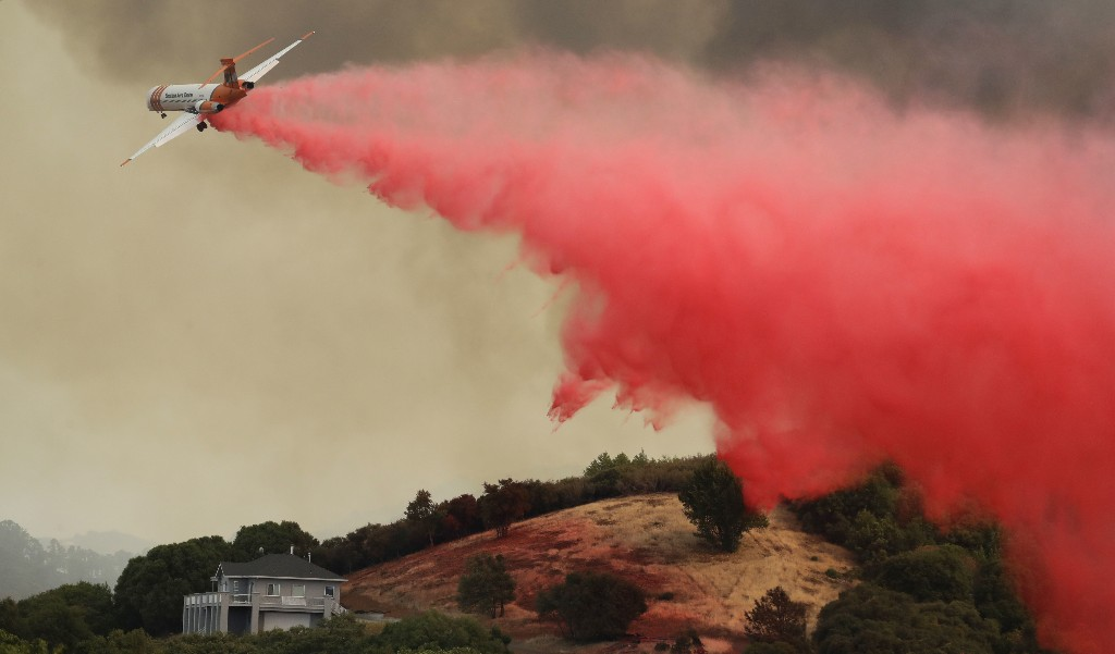 A plane drops retardant over a property threatened by a wildfire, Monday, July 30, 2018, in Lakeport, Calif. (AP Photo/Marcio Jose Sanchez)