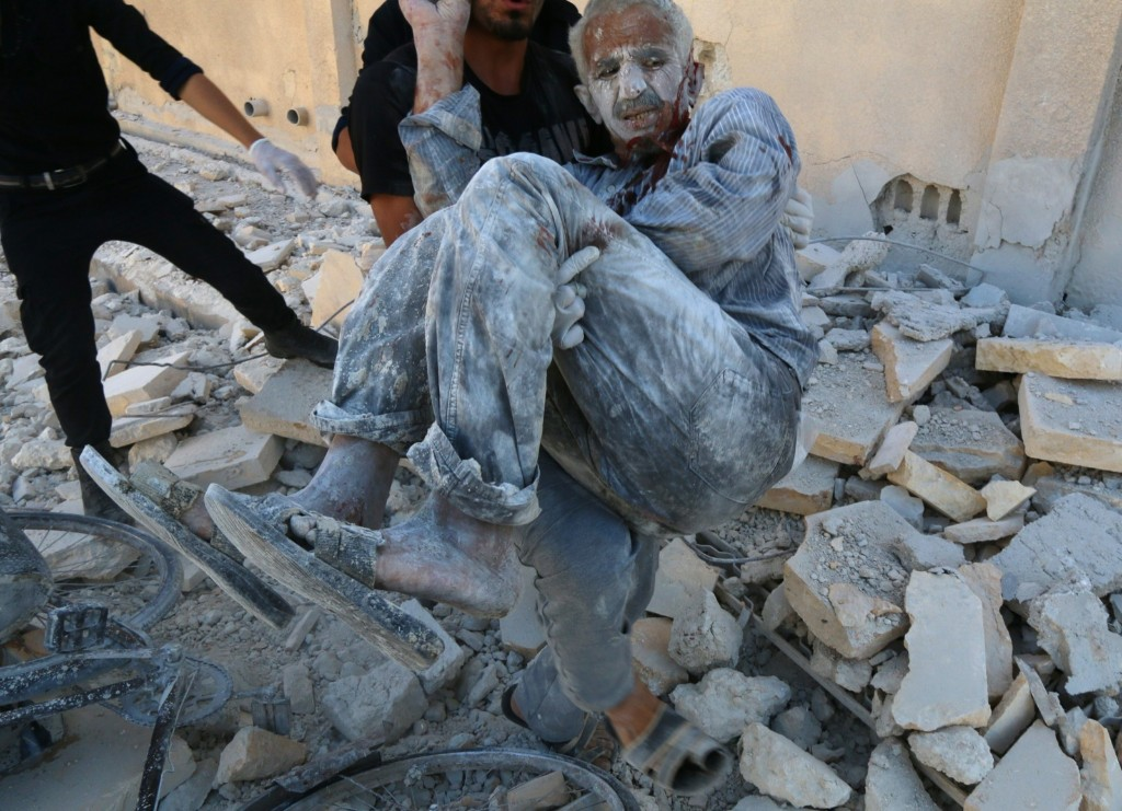 Civil defense workers rescue a man after a Syrian government helicopter allegedly dropped a barrel bomb in Aleppo. ZEIN AL-RIFAI/AFP/Getty Images