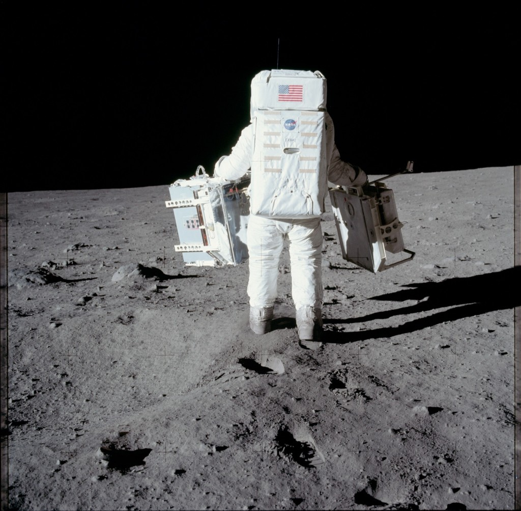 This photograph is the first in a sequence of pictures Neil Armstrong took of Buzz Aldrin from Apollo 11 carrying the EASEP out to the deployment site a short way south of the spacecraft. In this picture, he is walking across the raised rim of the small crater. NASA Photo