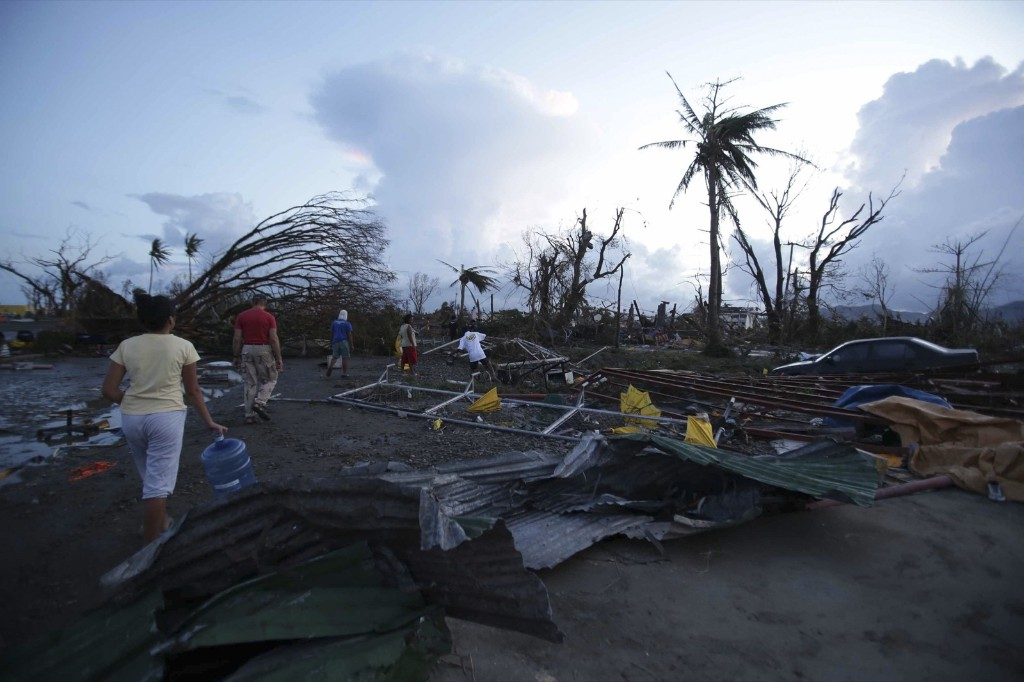 Residents walk by debris in Tacloban. AP Photo/Aaron Favila
