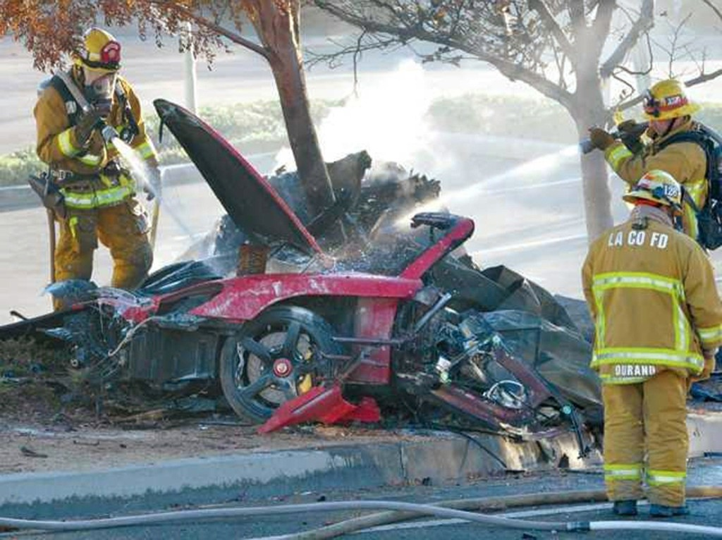 Firefighters extinguish the fire in the car where actor Paul Walker was killed in Valencia, California, Saturday. REUTERS/Dan Watson/The Santa Clarita Valley Signal
