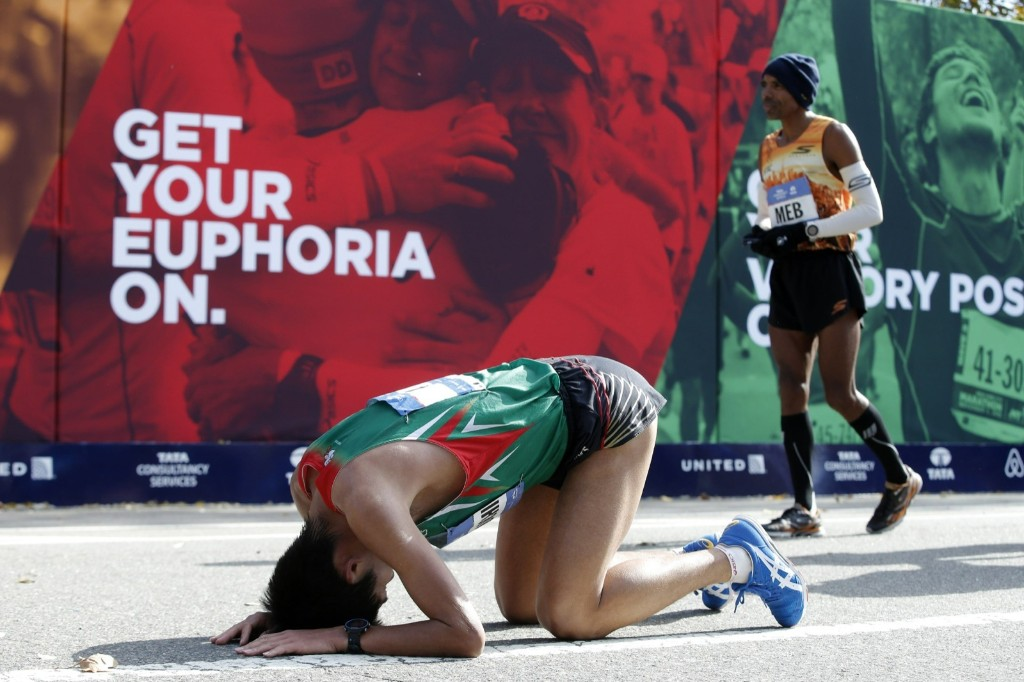 Yuki Kawauchi of Japan drops to his knees after finishing. REUTERS/Mike Segar
