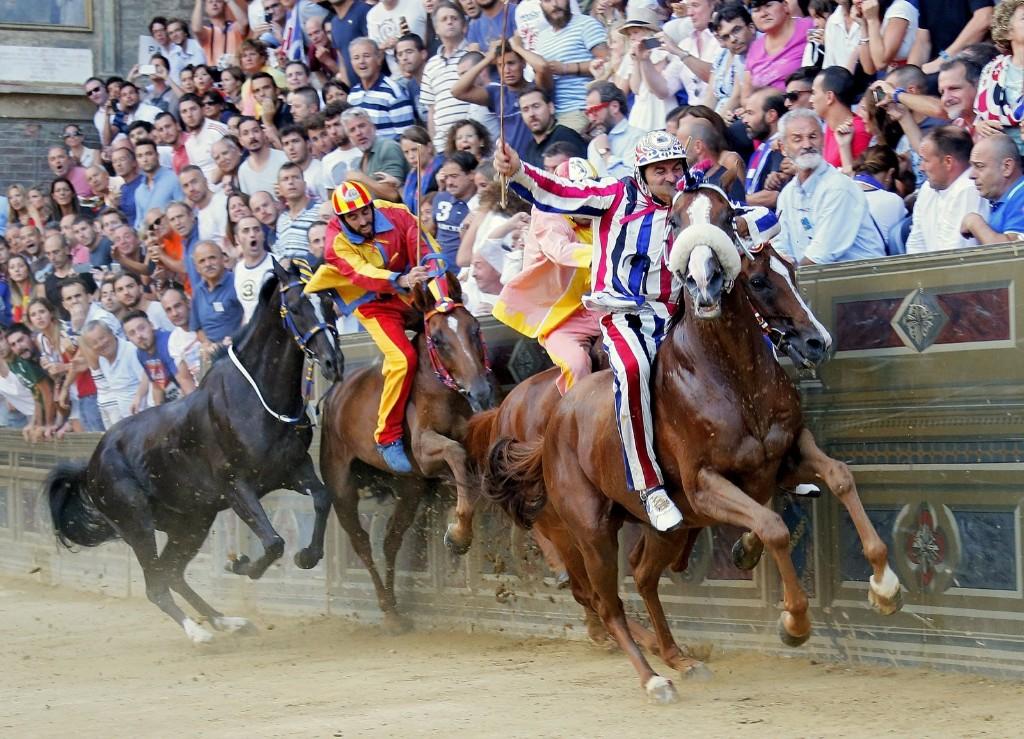 "Jockeys from ""Istrice"" (Porcupine) parish, ""Valdimontone"" (Ram) parish, Chiocciola (Snail) parish and Tartuca (Tortoise) parish compete as jockey Giovanni Atzeni of ""Selva"" (Forest) parish rides on his way to win the Palio di Siena horse race in Siena horse race in Siena August 17. REUTERS/Fabio Muzzi"
