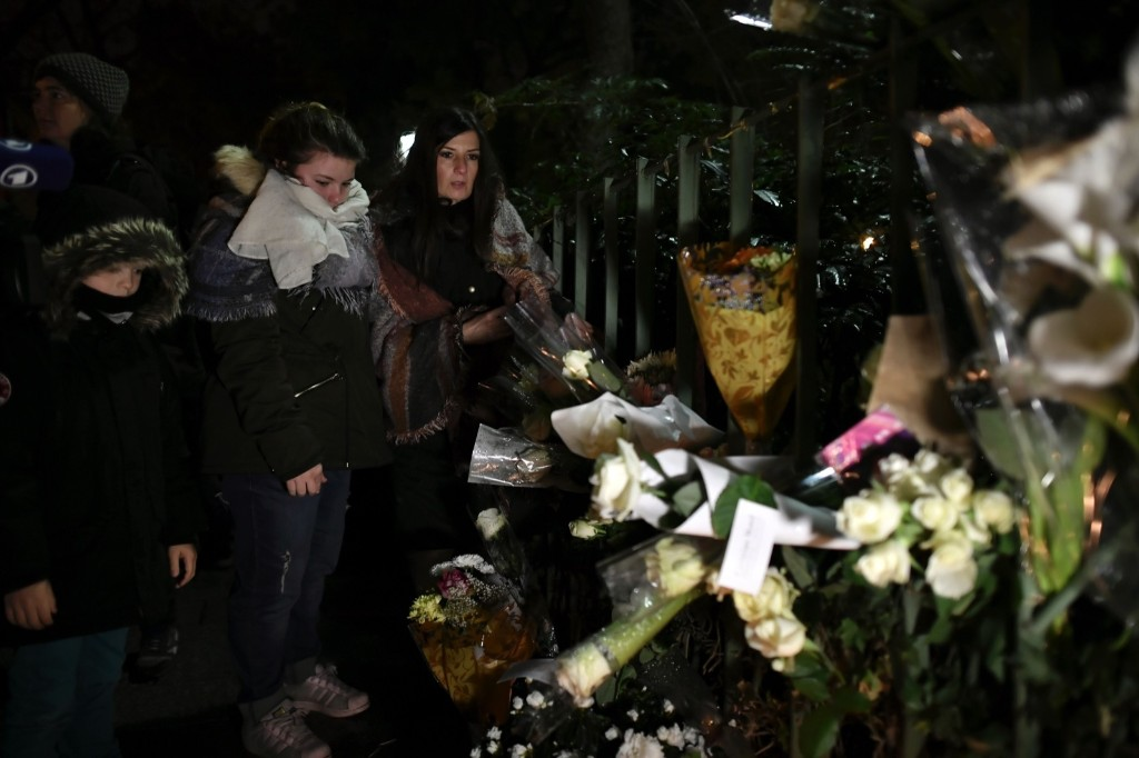 People gather around flowers and candles laid next to the Bataclan concert hall in Paris on the first anniversary of the Paris attacks. PHILIPPE LOPEZ/AFP/Getty Images