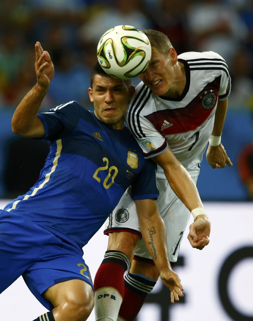 Argentina's Sergio Aguero jumps for the ball with Germany's Bastian Schweinsteiger. REUTERS/Eddie Keogh