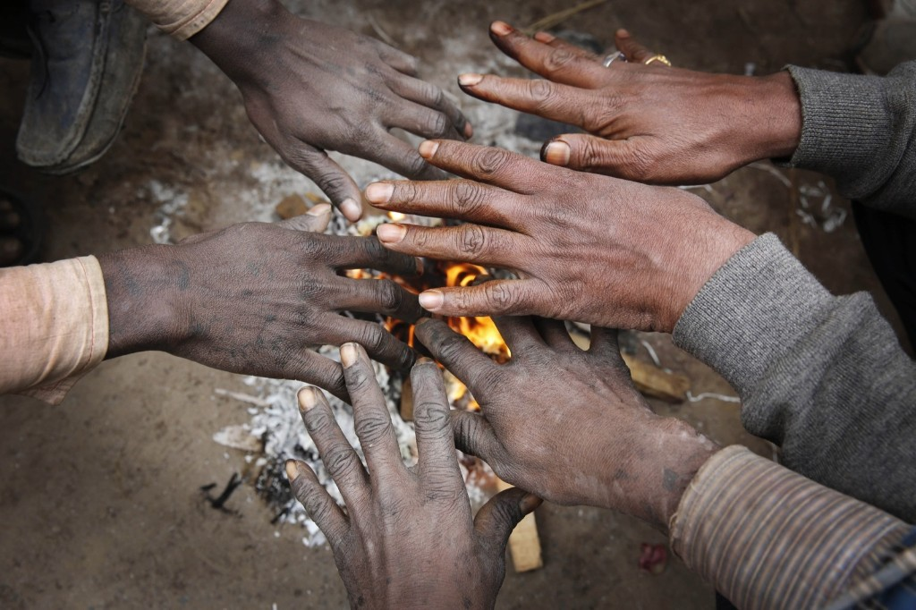Indian men warm their hands near a bonfire on a cold and foggy morning in Allahabad. AP Photo/Rajesh Kumar Singh