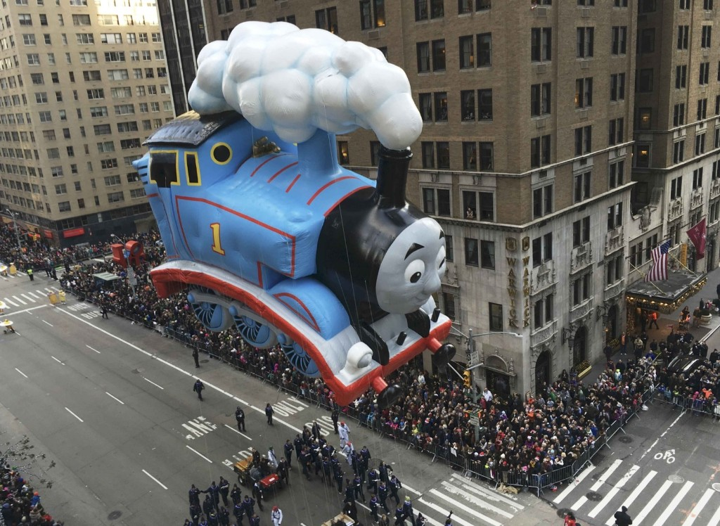 "A float depicting the animated character ""Thomas the Train"" proceeds along 6th Ave as spectators watch from buildings during the 89th Macy's Thanksgiving Day Parade in the Manhattan borough of New York, Thursday REUTERS/Carlo Allegri"