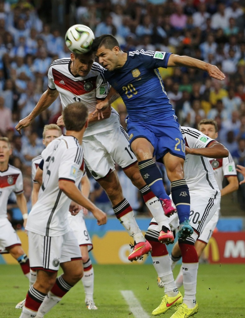 Germany's Miroslav Klose jumps for the ball with Argentina's Sergio Aguero. REUTERS/Sergio Moraes
