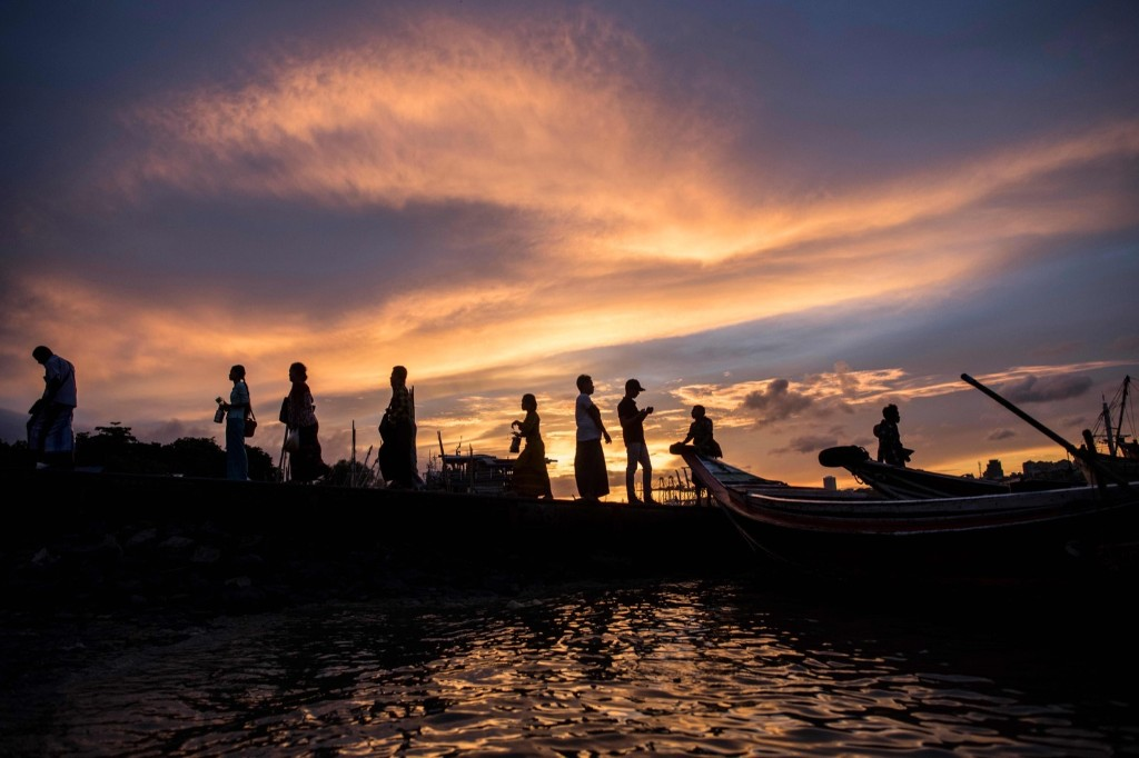 People arrive at a jetty to cross the Yangon River on boats during sunset in Yangon, Myanmar. YE AUNG THU/AFP/Getty Images