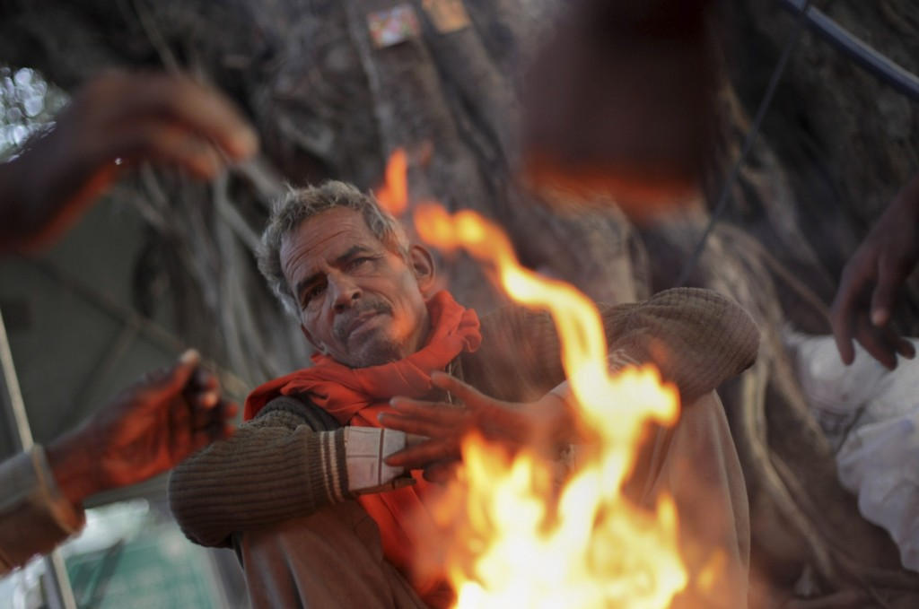 An Indian man warms himself near a bonfire early morning in New Delhi, Wednesday. AP Photo/Tsering Topgyal