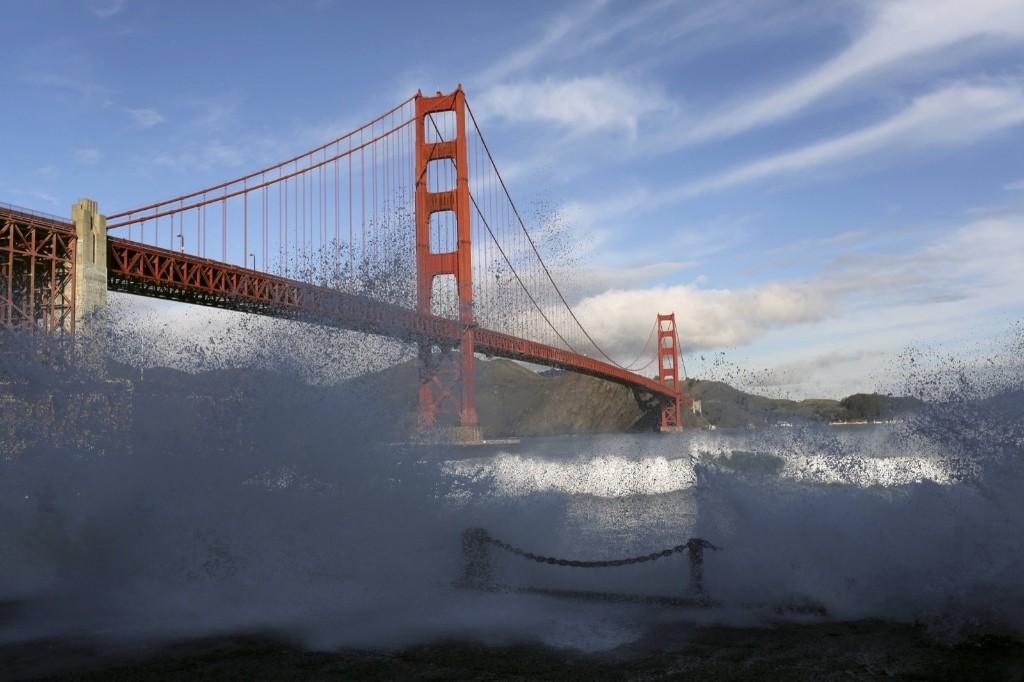 Waves crash against a sea wall in San Francisco Bay beneath the Golden Gate Bridge. REUTERS/Robert Galbraith