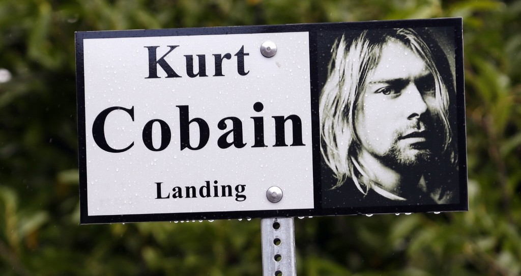 "A sign marks the location of ""Kurt Cobain Landing,"" a tiny park near his childhood home. AP Photo/Elaine Thompson"