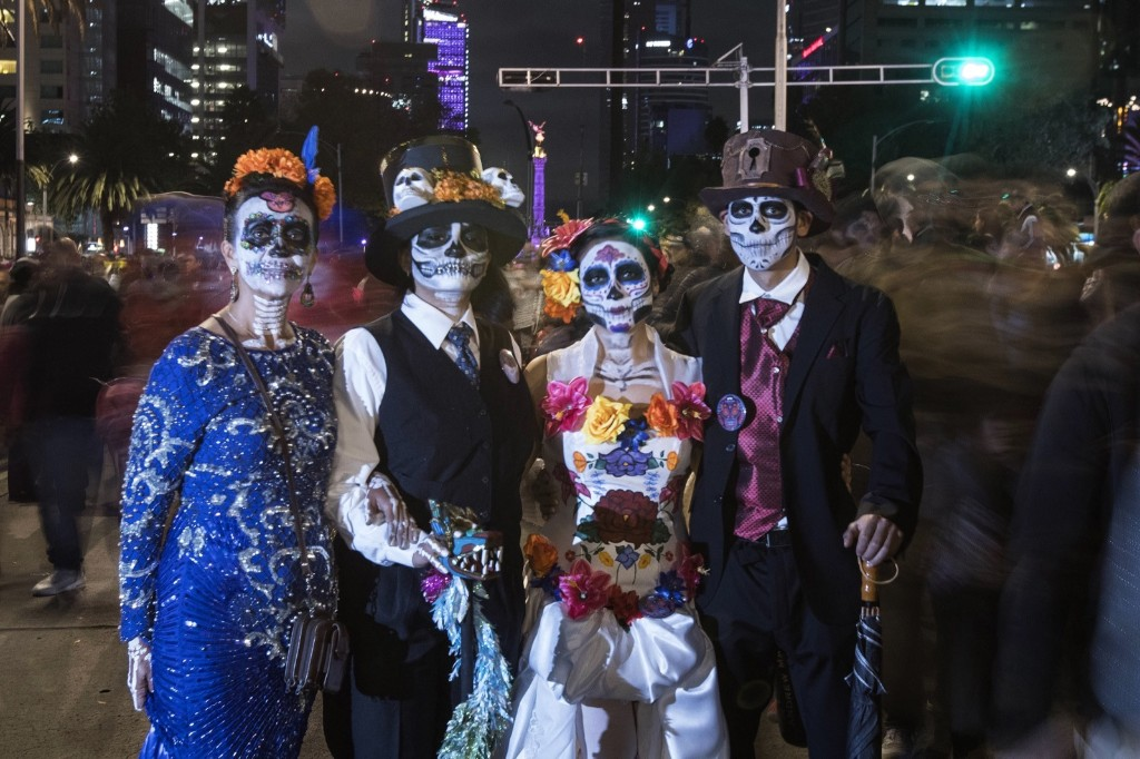 A family during the annual Catrinas Parade, as part of Day of the Dead celebrations, culminating with visits to the graves of departed loved ones on Nov. 1 and 2. AP Photo/Christian Palma