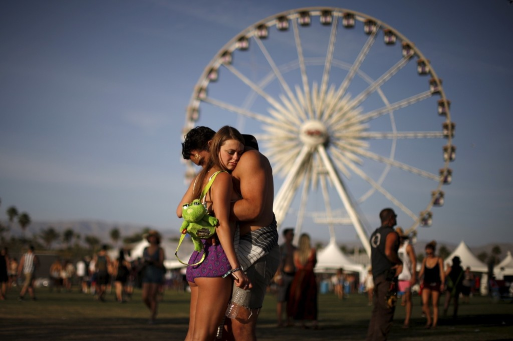 A couple hugs in front of the ferris wheel at the Coachella Valley Music and Arts Festival. REUTERS/Lucy Nicholson