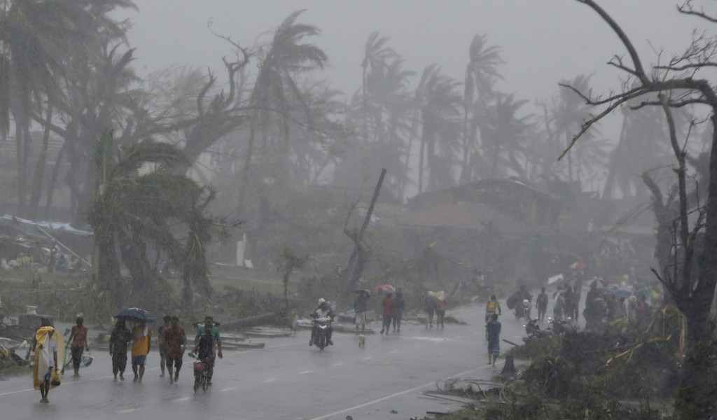 Survivors walk on a road in a heavy downpour after Typhoon Haiyan battered Tacloban city in central Philippines. One of the most powerful storms ever recorded has killed at least 10,000 people a senior police official said on Sunday. REUTERS/Erik De Castro