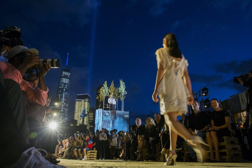 A model presents a creation from the Givenchy Spring/Summer 2016 collection as the Tribute in Light installation shines next to One World Trade in the background. REUTERS/Lucas Jackson