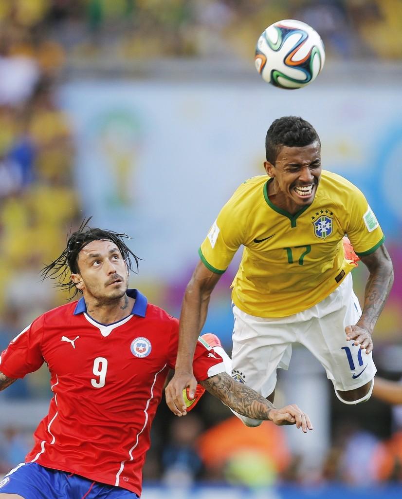 Brazil's Luiz Gustavo and Chile's Mauricio Pinilla go up for a header. AP Photo/Frank Augstein