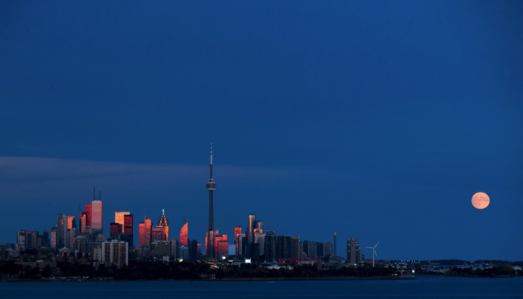 The moon rises behind the skyline in Toronto. REUTERS/Mark Blinch