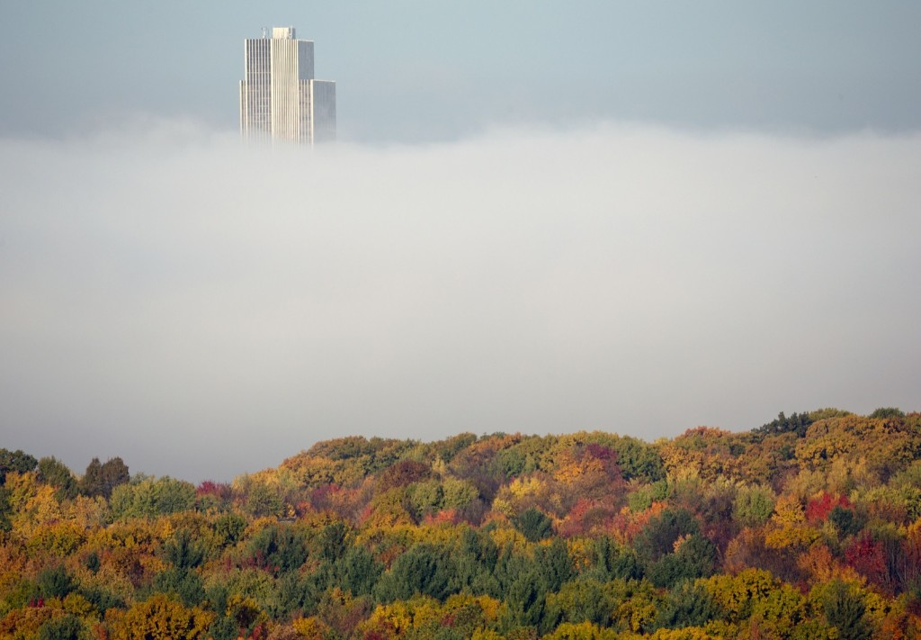 The Corning Tower at the Empire State Plaza in Albany, NY is shrouded in autumn colors and morning fog from the Hudson River. AP Photo/Mike Groll