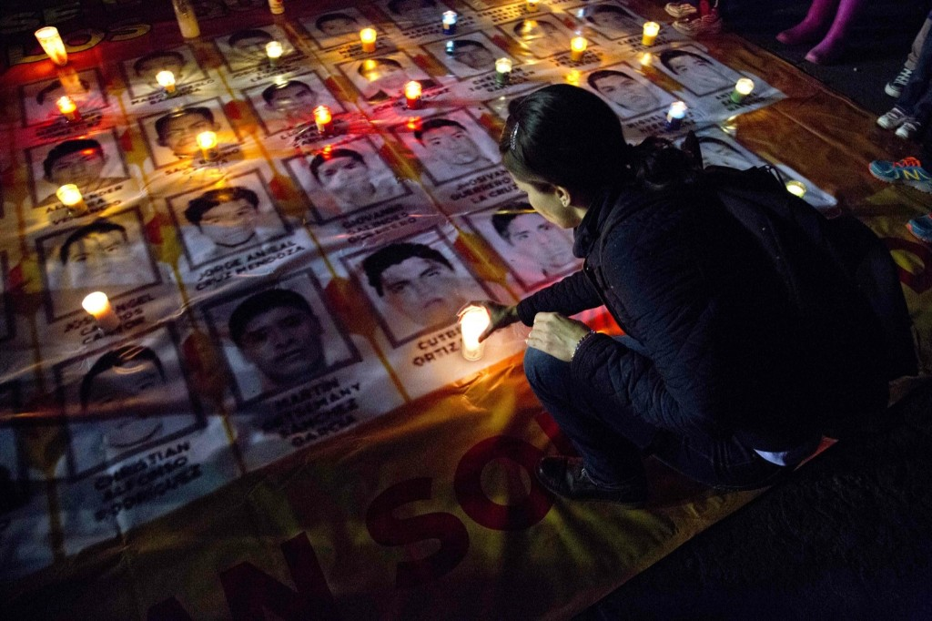 A woman places a candle at a tribute for the 43 missing students from the Isidro Burgos rural teachers college, in Mexico City. AP Photo/Eduardo Verdugo