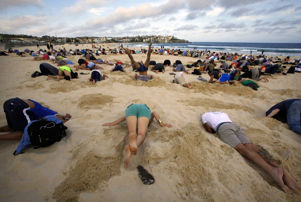 A group of demonstrators participate in a protest of the G20 summit by burying their heads in the sand on Sydney's Bondi Beach. REUTERS/David Gray