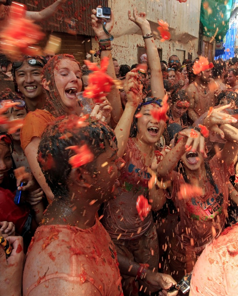 "Crowds of people throw tomatoes at each other, during the annual ""tomatina"" tomato fight fiesta, in the village of Bunol, 50 kilometers outside Valencia, Spain, Wednesday. AP Photo/Alberto Saiz"