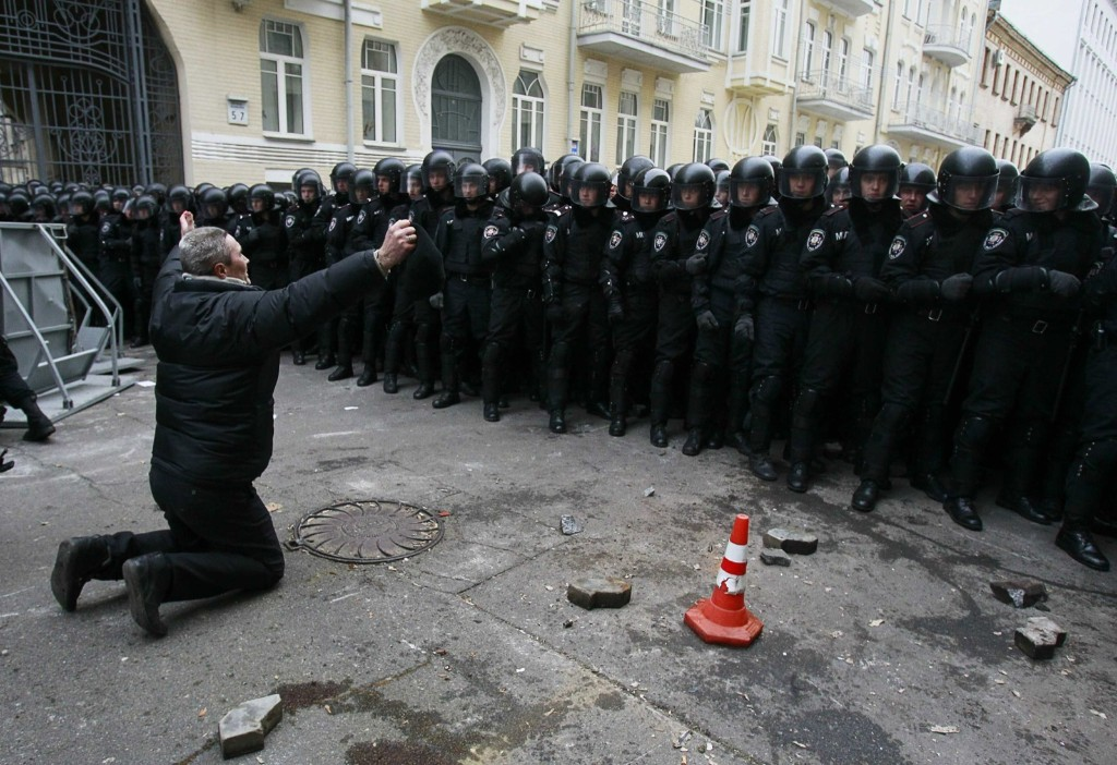 A man kneels down while riot police stand guard near the presidential administration building during a rally held by supporters of EU integration in Kiev, Sunday. REUTERS/Gleb Garanich