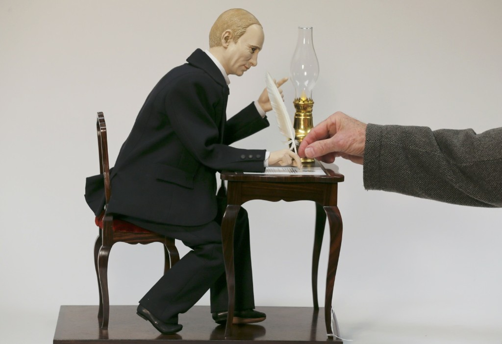 Uwe Breker, the world's leading auctioneer of technical antiques, fixes the quill pen to a contemporary musical automaton depicting Russian President Vladimir Putin, in Cologne. REUTERS/Wolfgang Rattay