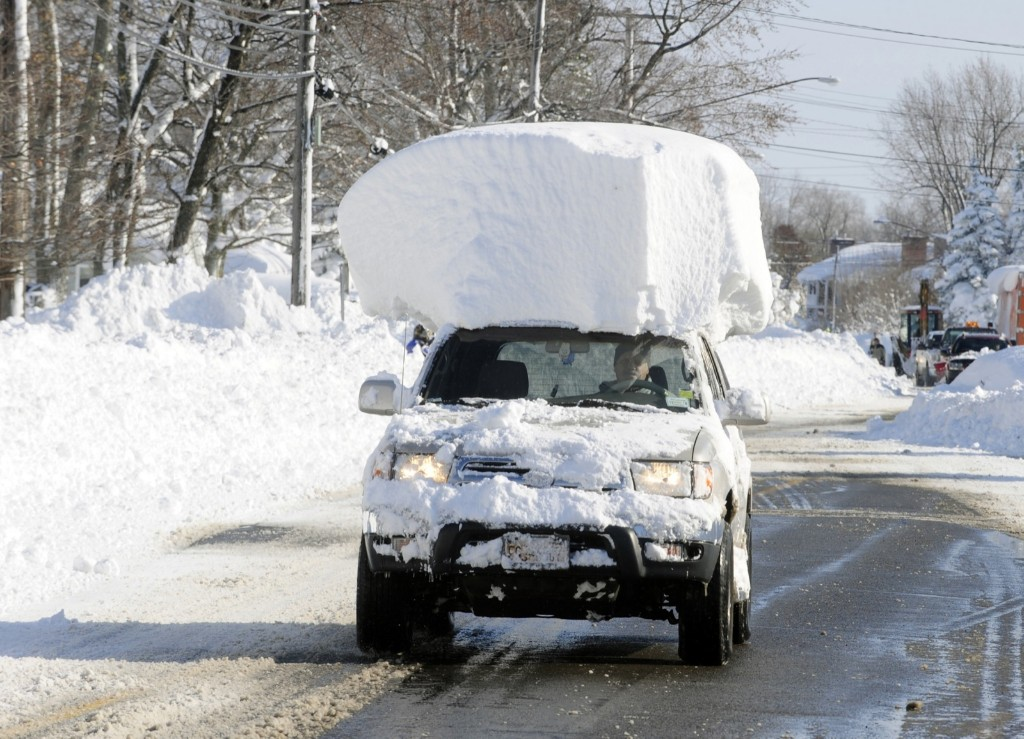 A vehicle drives along Route 20 after digging out after a massive snow fall in Lancaster, N.Y. AP Photo/Gary Wiepert