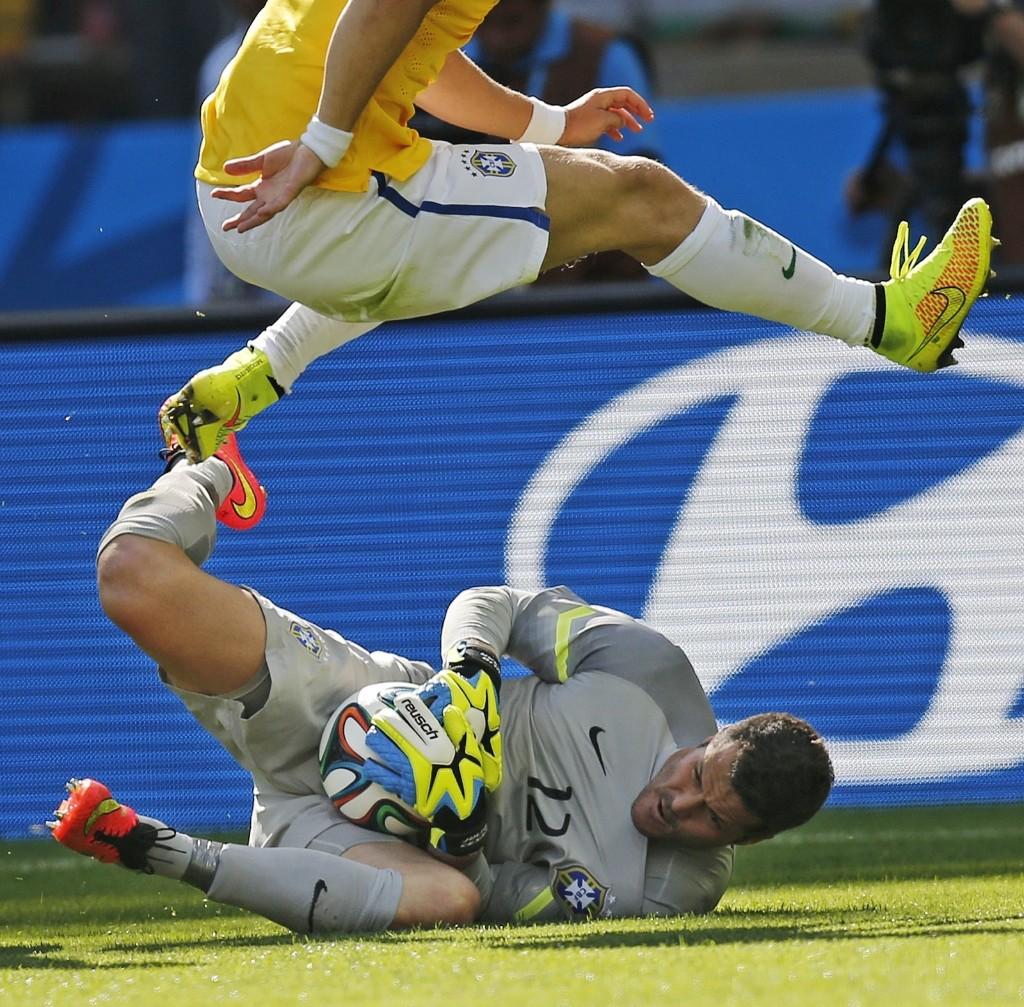 Brazil's David Luiz jumps over goalkeeper Julio Cesar. AP Photo/Frank Augstein