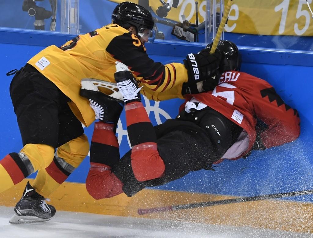 Germany's Felix Schutz checks Canada's Maxim Noreau during men's semifinals. JUNG YEON-JE/AFP/Getty Images
