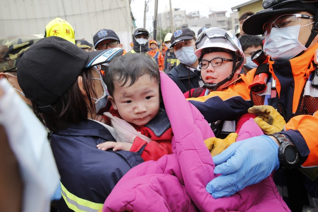 A baby boy is rescued from a collapsed building. AP Photo/Wally Santana