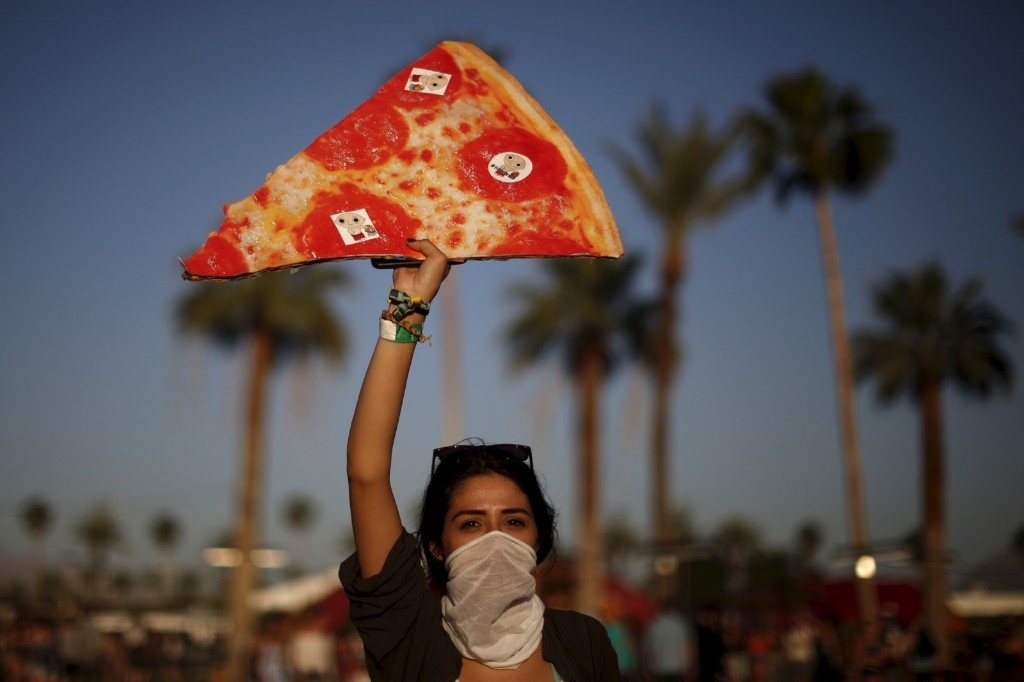 A woman carries a replica slice of pizza in order to find separated friends in the crowd. REUTERS/Lucy Nicholson