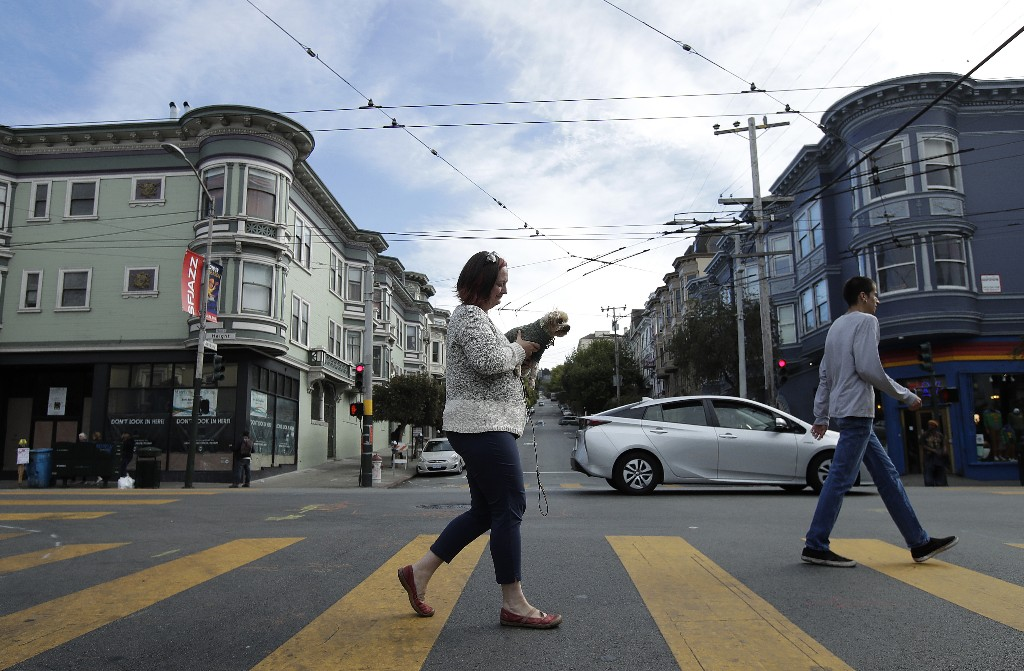 In this Oct. 1, 2018 photo, Christin Evans, owner of The Booksmith, carries her dog Joey Pistachio as she crosses Ashbury Street along Haight Street in San Francisco. A measure on San Francisco's Nov. 6 ballot would levy an extra tax on hundreds of the city's wealthiest companies to raise $300 million for homelessness and mental health services. It's the latest battle between big business and social services advocates who say that companies such as Amazon, Google and Salesforce can afford to help solve severe inequities caused by business success. (AP Photo/Jeff Chiu)