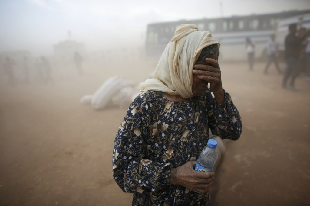 A Kurdish Syrian refugee covers her face as she waits for transport during a sand storm on the Turkish-Syrian border. REUTERS/Murad Sezer
